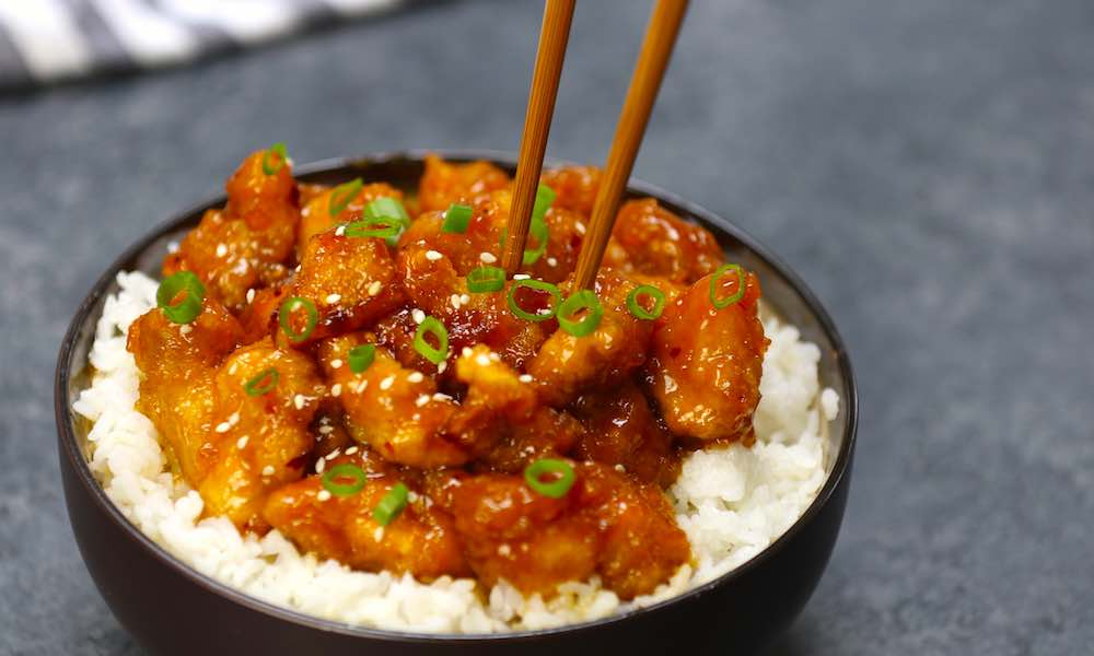 General Tso Chicken Crock Pot - this photo shows this dish served on top of white rice and garnished with minced green onion and sesame seeds, with chopsticks going in to pick up a piece. A tangy and flavorful slow cooker recipe to feed the entire family.
