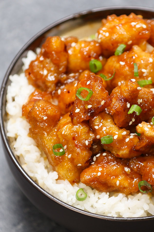 General Tso's Chicken - this photo shows a closeup of crispy chicken pieces with minced green onions and sesame seeds in a sticky sauce on top of white rice served in a bowl for a delicious weeknight dinner idea that's easy to make in 20 minutes