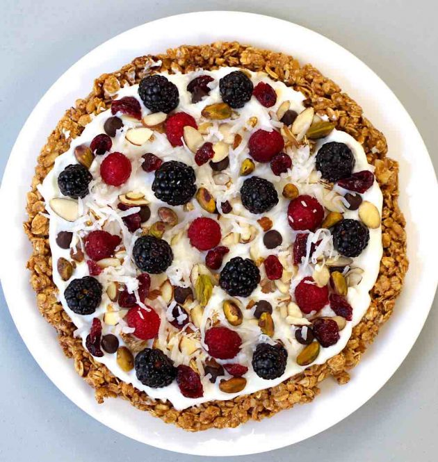 Healthy Granola Breakfast Pizza – A healthy and delicious recipe that's easy to make with a few simple ingredients: granola, peanut butter, almonds, cinnamon, yogurt, berries and nuts. A perfect, vegetarian breakfast or brunch idea. So yummy! Video recipe. | tipbuzz.com