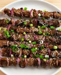 Grilled Garlic Beef Kabobs – Incredibly delicious beef skewers that are so easy to make! Nothing is better than these kabobs to serve on a warm summer day! All you need is some simple ingredients: steak, soy sauce, garlic, red onions, green onions, sesame seeds, sugar, ginger and oil. So Good! Quick and easy recipe, video recipe. | Tipbuzz.com