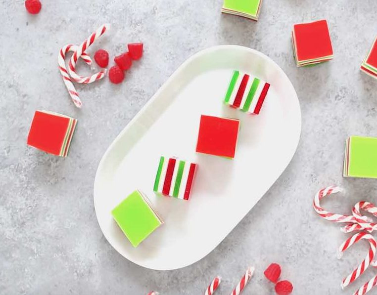 Christmas jello shots on a serving platter showing off their beautiful red, green and white layers