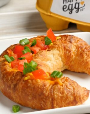 Holiday Croissant Boats are a mouthwatering breakfast recipe featuring fluffy ham and cheese omelet baked to golden perfection inside a flakey croissant and then topped with minced tomatoes and green onion for a colorful red and green holiday theme
