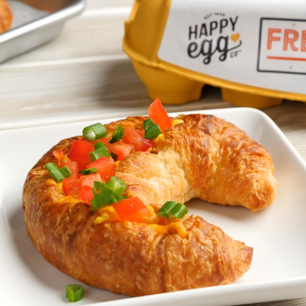 Holiday Croissant Boats are a baked breakfast with fluffy ham and cheese omelet baked inside of a crispy croissant