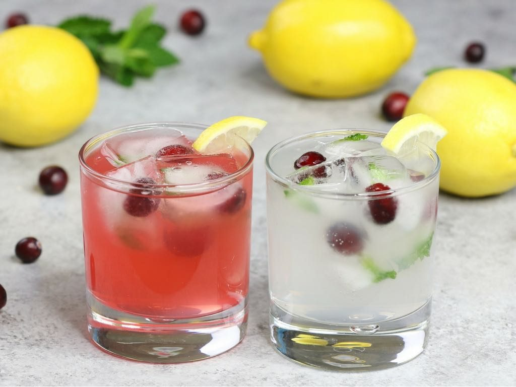 Lemonade cocktails made two ways with Mike's Hard Lemonade original flavor and strawberry flavor, garnished with cranberries and mint