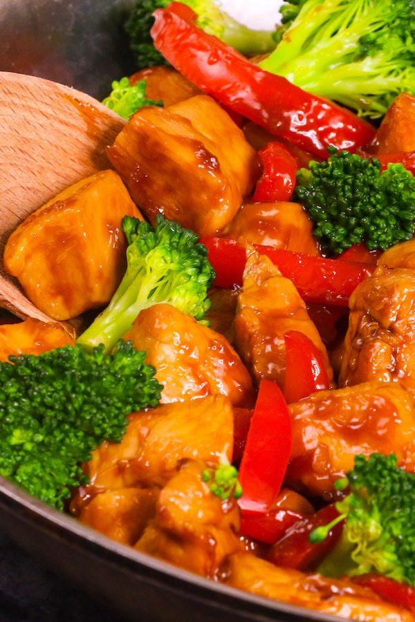 Closeup of cubed chicken breast and vegetables coated in honey garlic sauce for a delicious chicken vegetable stir fry