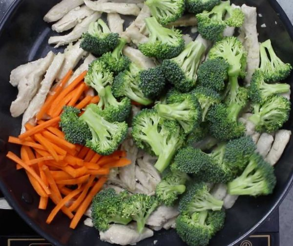 Honey Garlic Chicken - this photo shows mixing broccoli and carrots into chicken stir fry in a skillet