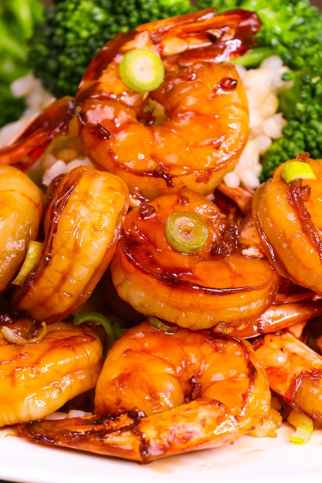 Closeup of honey garlic shrimp perfectly glazed and served on a bed of steamed rice with a side of broccoli