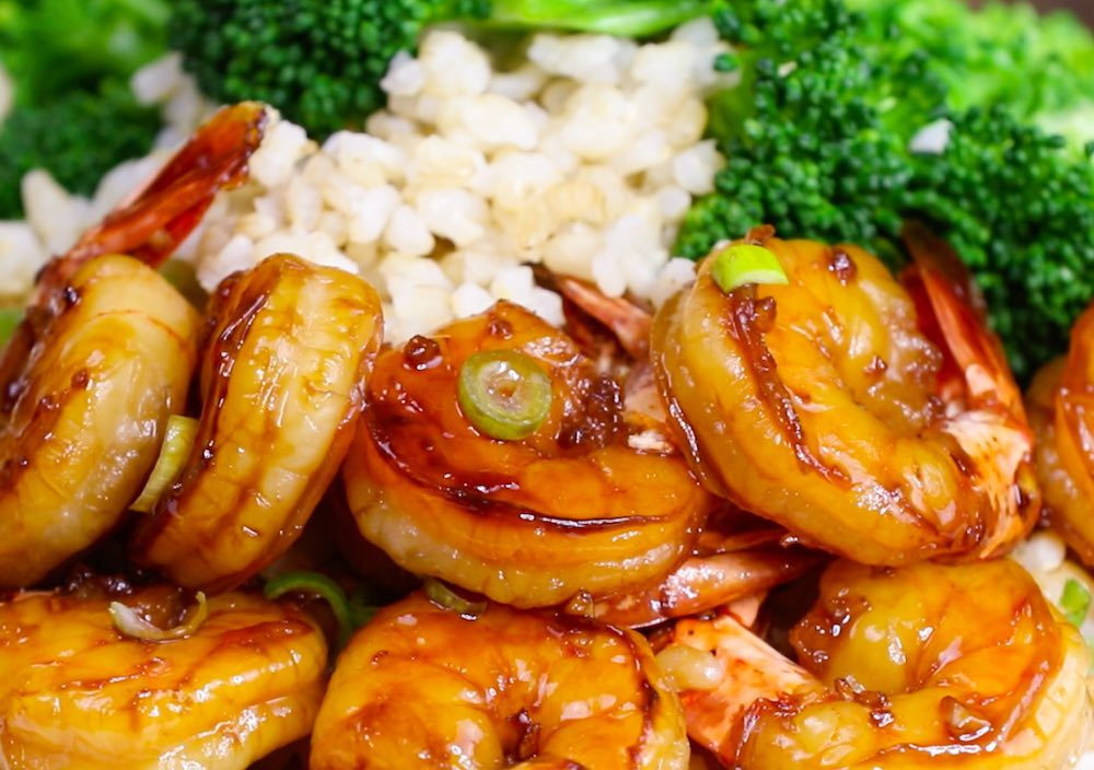 Honey Garlic Shrimp - this photo shows a serving presentation with minced green onions on top of brown rice with broccoli to make a complete meal