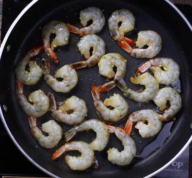 Raw shrimp in a single layer in a skillet being cooked when making a Honey Garlic Shrimp Stir Fry