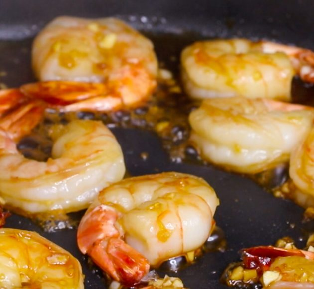 Closeup photo of jumbo shrimp being sauteed in a skillet when making Honey Garlic Shrimp Stir Fry