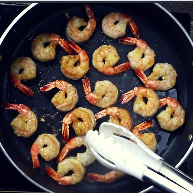 This is a photo of honey garlic shrimp cooking in a frying pan with tongs being used to turn them for even cooking