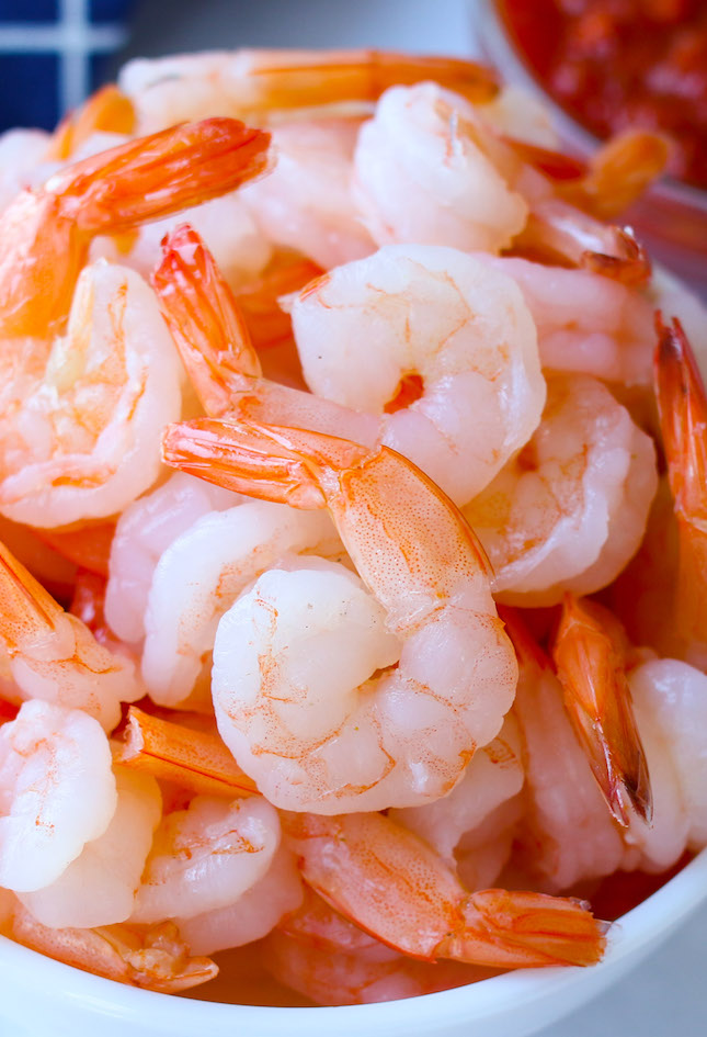 Medium-size, peeled, tail-on shrimp in a bowl after boiling with a beautiful orange-pink color
