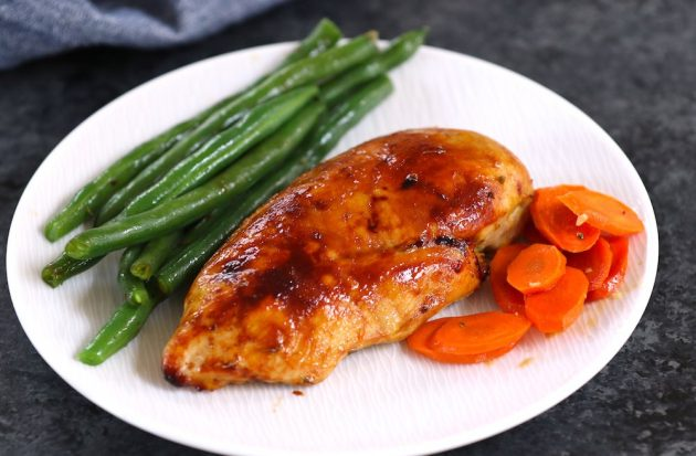 This photo shows baked chicken breast with crispy skin served with carrots and green beans on a plate