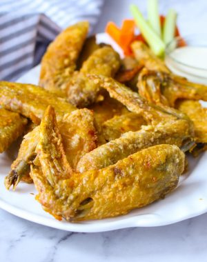 Crispy baked chicken wings on a serving platter with carrots, celery and ranch dip
