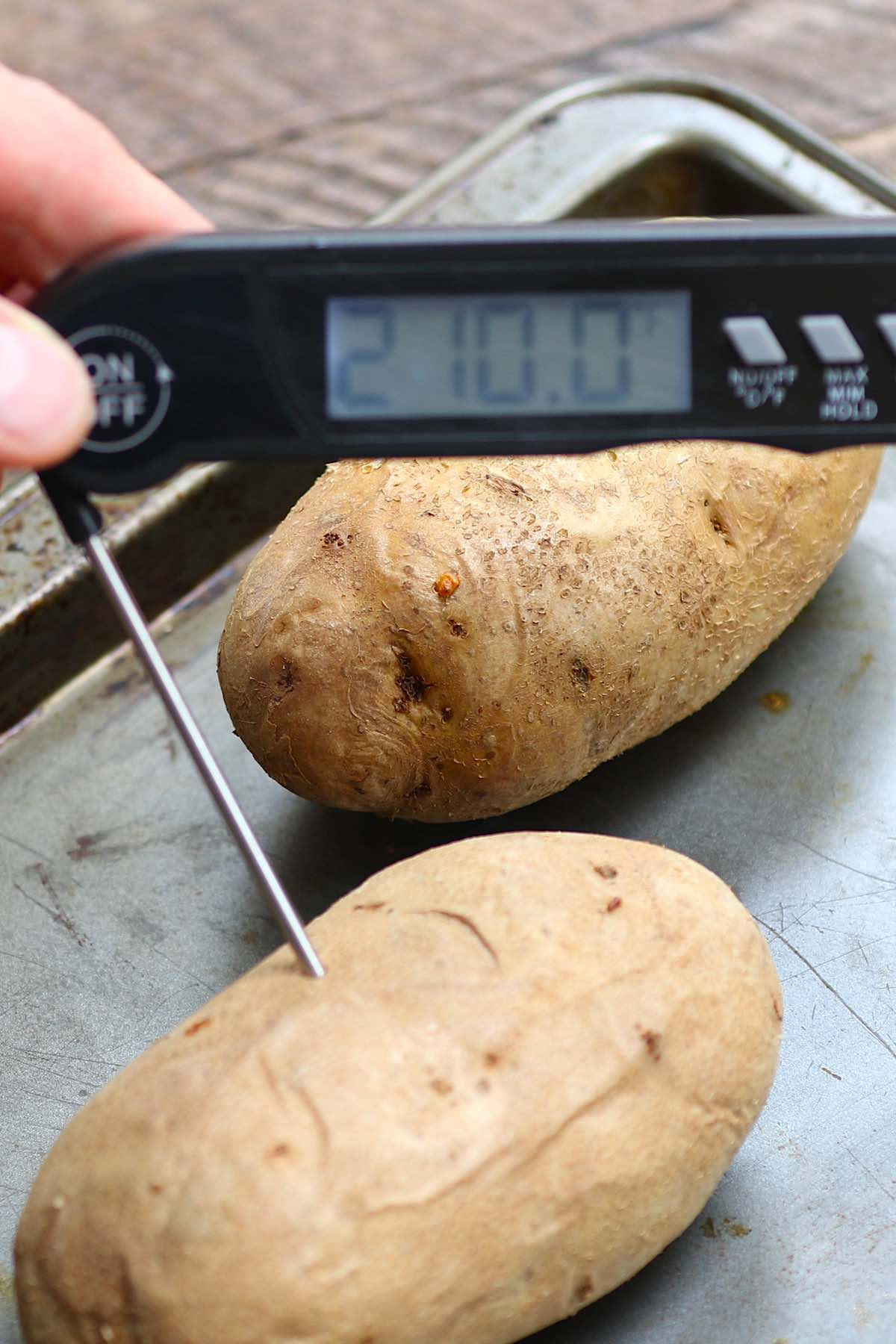 Inserting an instant-read thermometer into the middle of a potato to determine how long to bake a potato. It's done at 210 degrees F.
