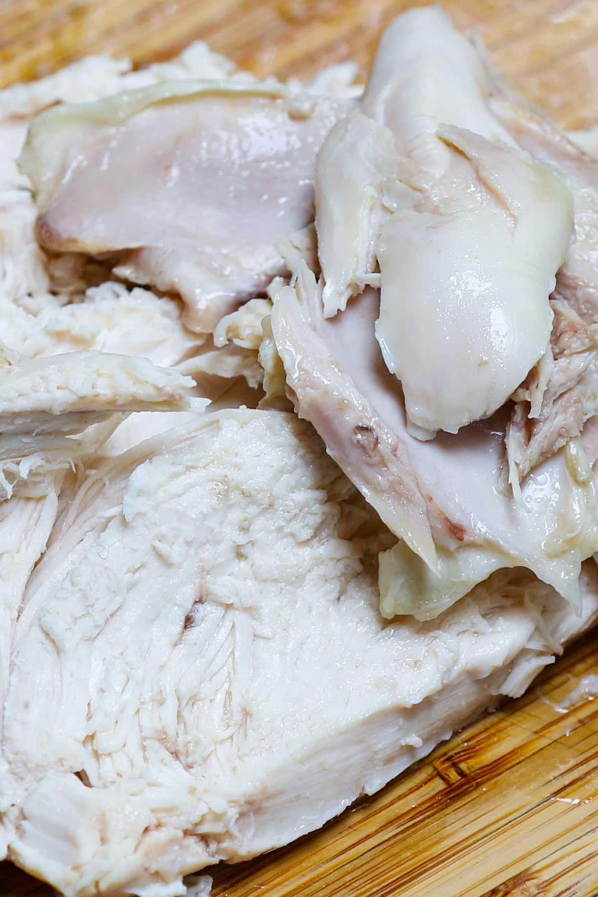 Tender and juicy boiled chicken carved into slices for serving