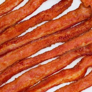 Learn how long to cook bacon in the oven with this handy guide! We also cover tips on how to cook bacon easily including temperature, cuts, tips and tricks. Whether you prefer crispy or chewy oven baked bacon, read on for all the tips you need!