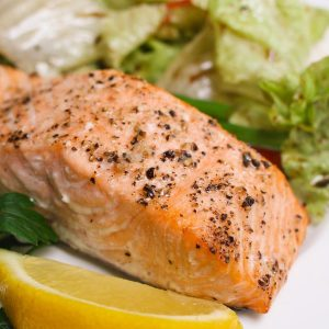 Oven baked salmon on a serving plate with a side salad