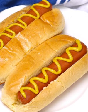 Perfectly boiled hot dogs in buns and dressed with mustard