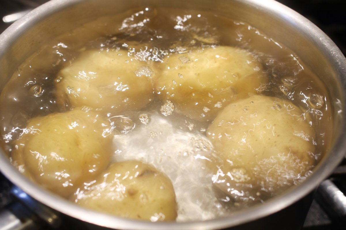 Closeup of round white potatoes in a pot full of boiling water