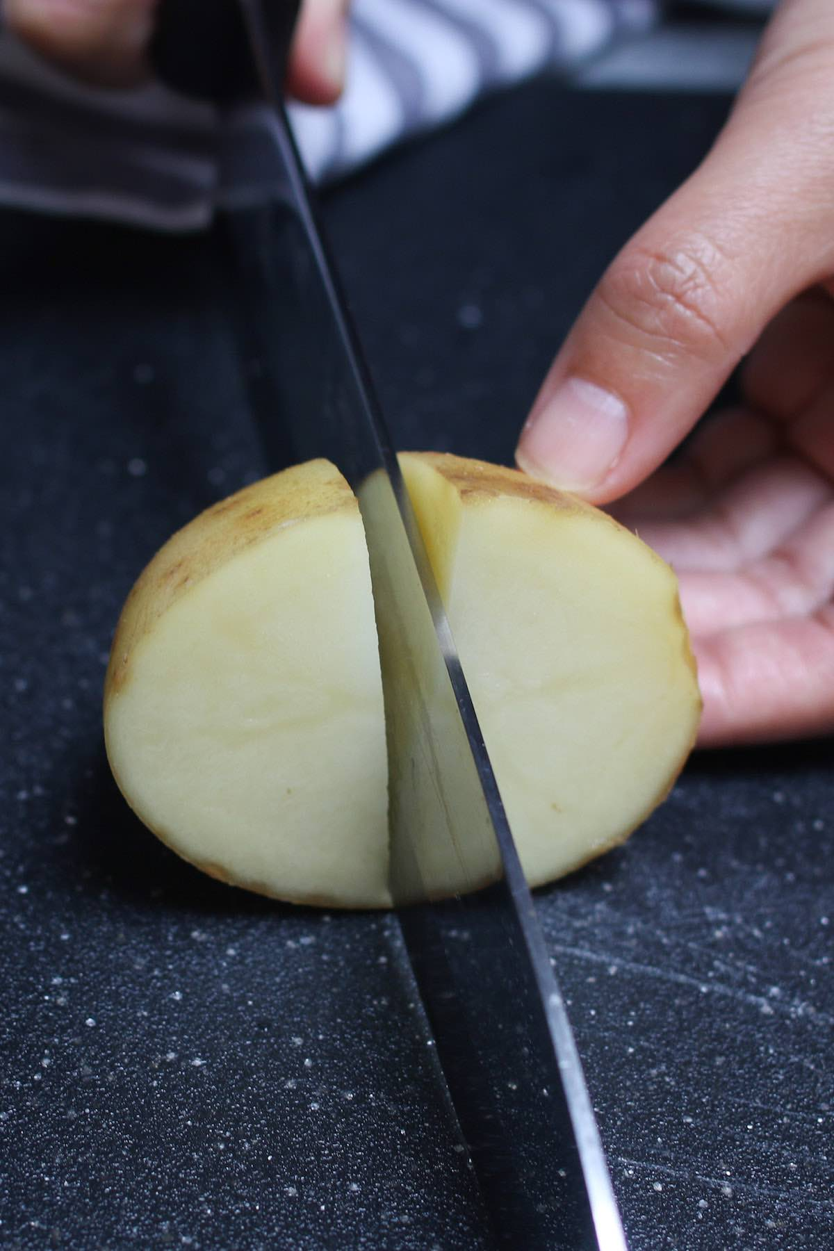 Cutting a raw white potato into quarters with a chef's knife for faster boiling