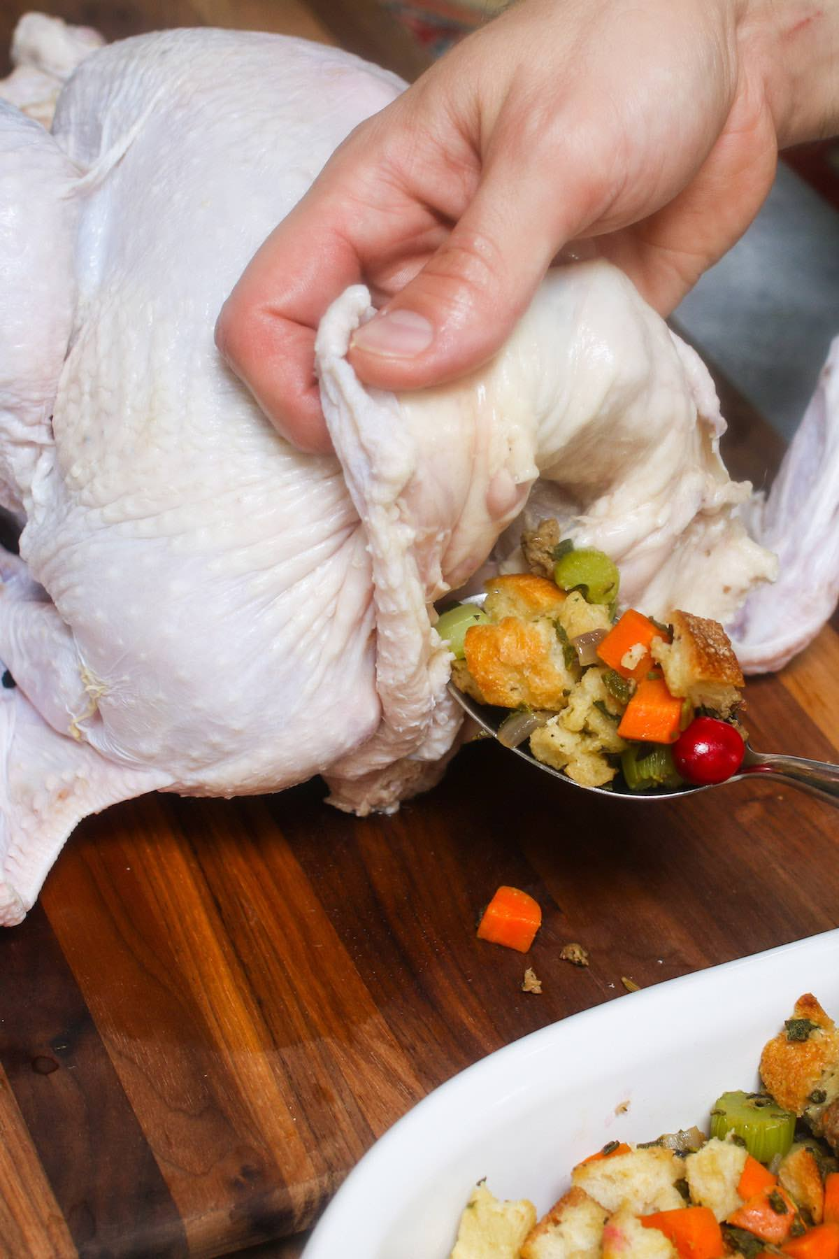 Stuffing a turkey from the neck end by lifting the flap of skin to expose the cavity