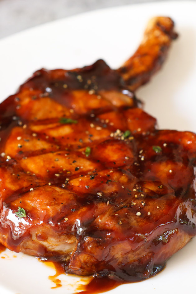 A tender and juicy, bone-in grilled pork chop on a plate resting before serving