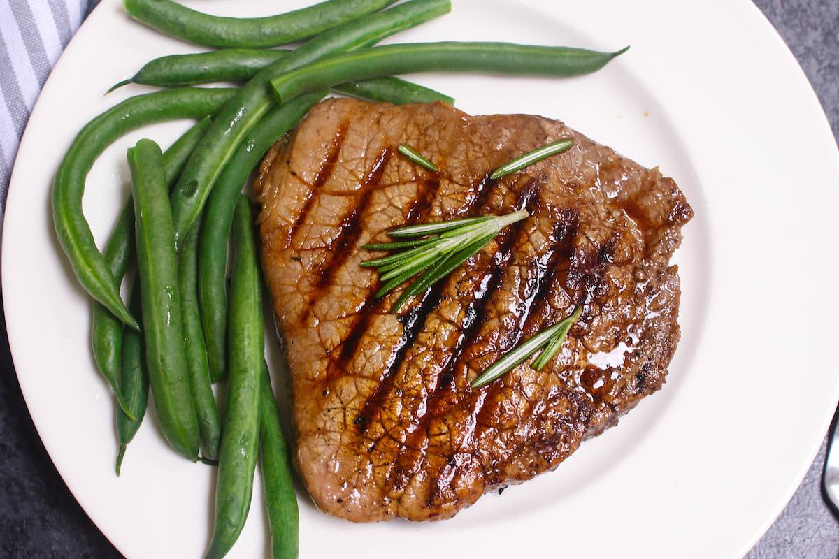 Overhead view of a grilled round steak on a serving plate with green beans as an example of a tougher cut made tender using marinating