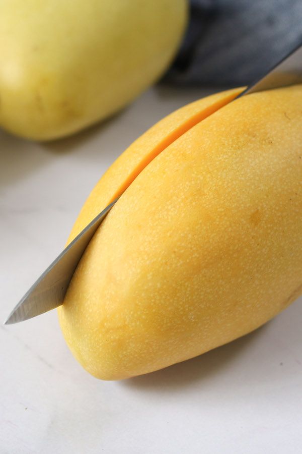 This photo shows cutting vertically about 1/4 inch from the middle, so as to cut along the pit of the mango