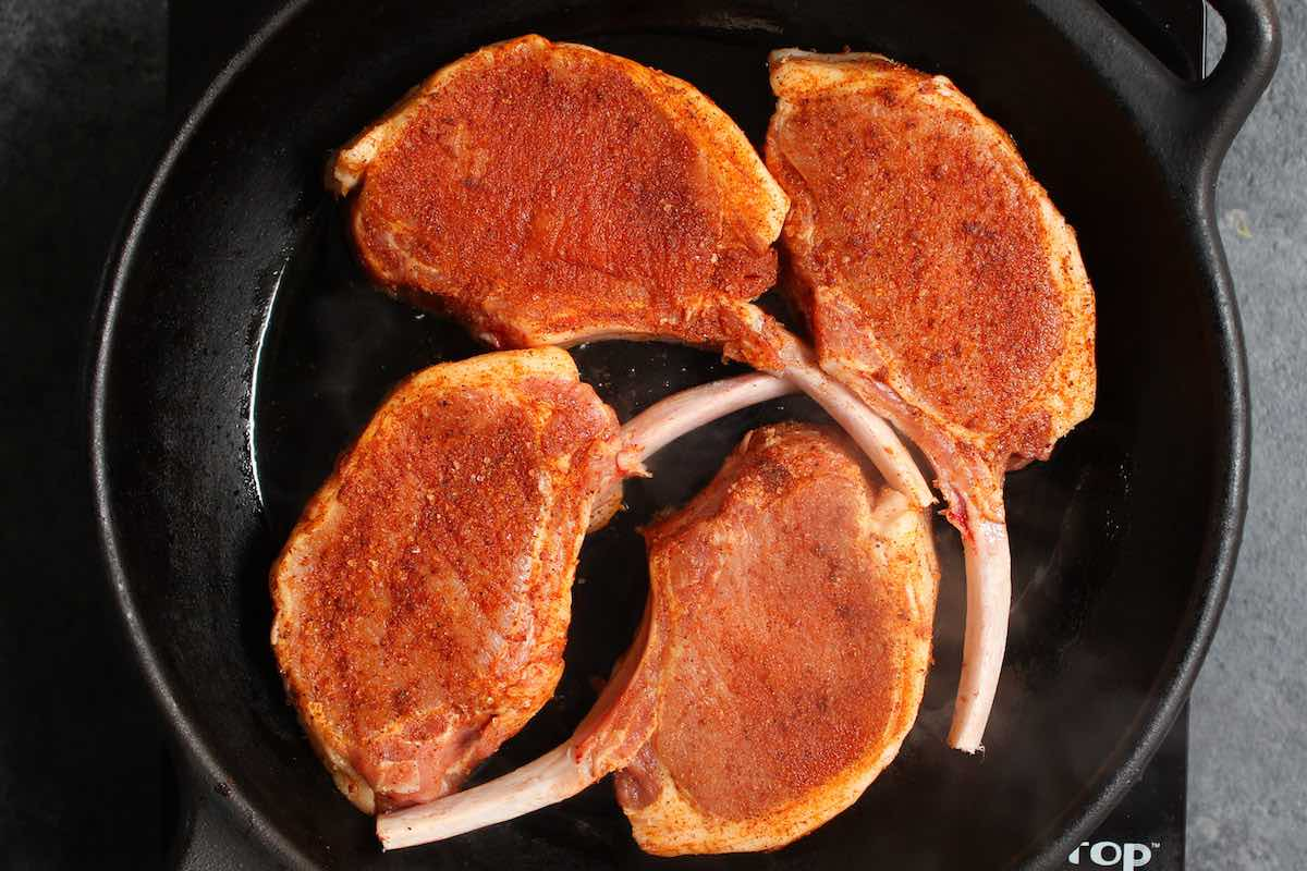 Overhead photo showing four seasoned bone-in rib chops frying in a cast iron skillet