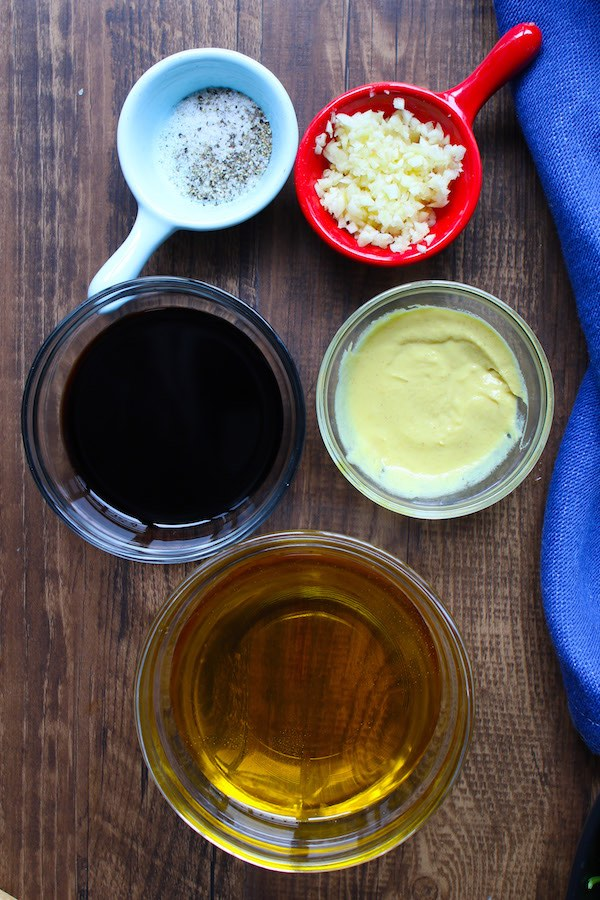 The ingredients for making balsamic vinaigrette: balsamic vinegar, extra virgin olive oil, dijon mustard, minced garlic, salt and pepper