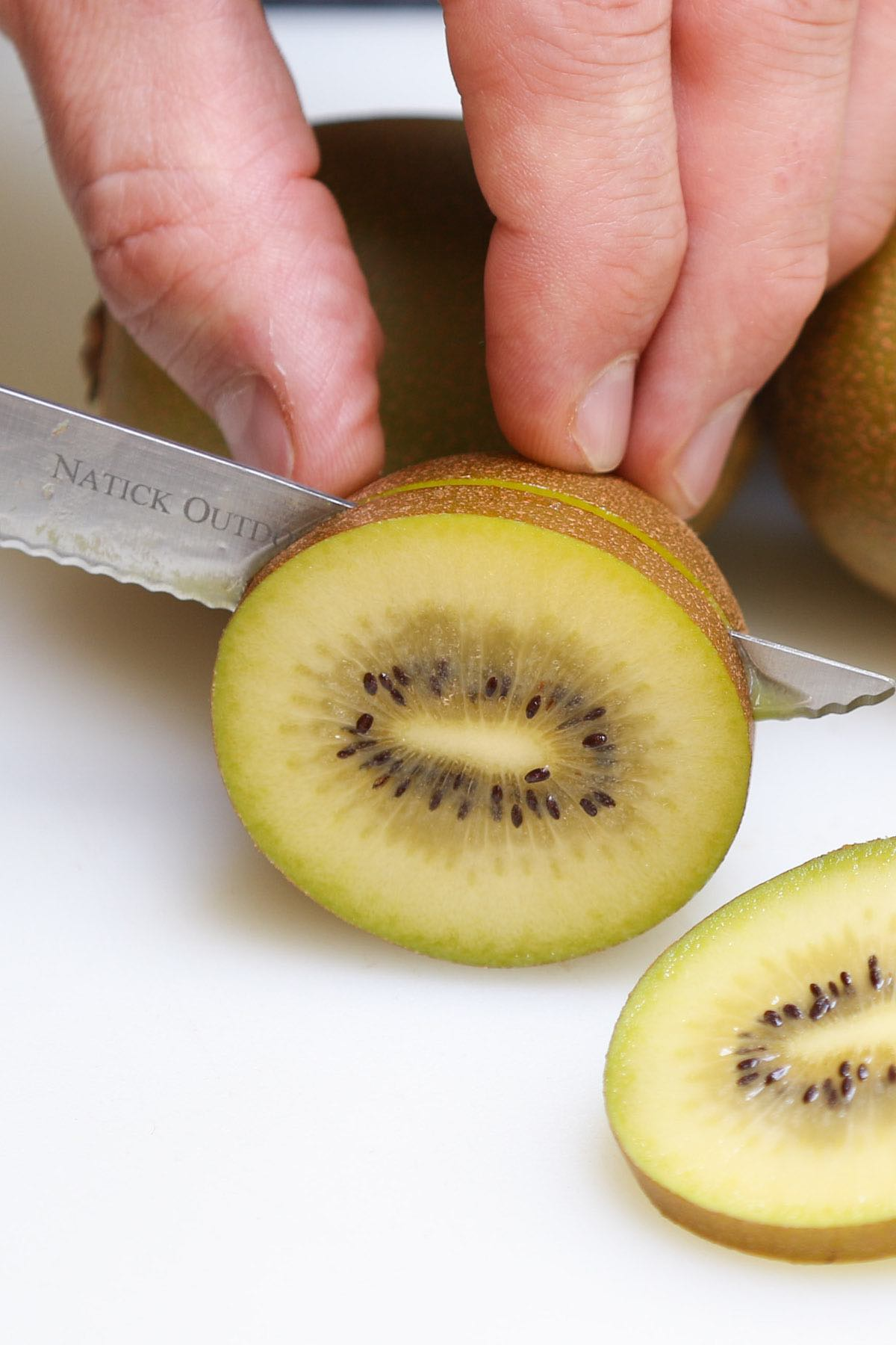 Slicing a kiwi widthwise with a paring knife while leaving the skin on
