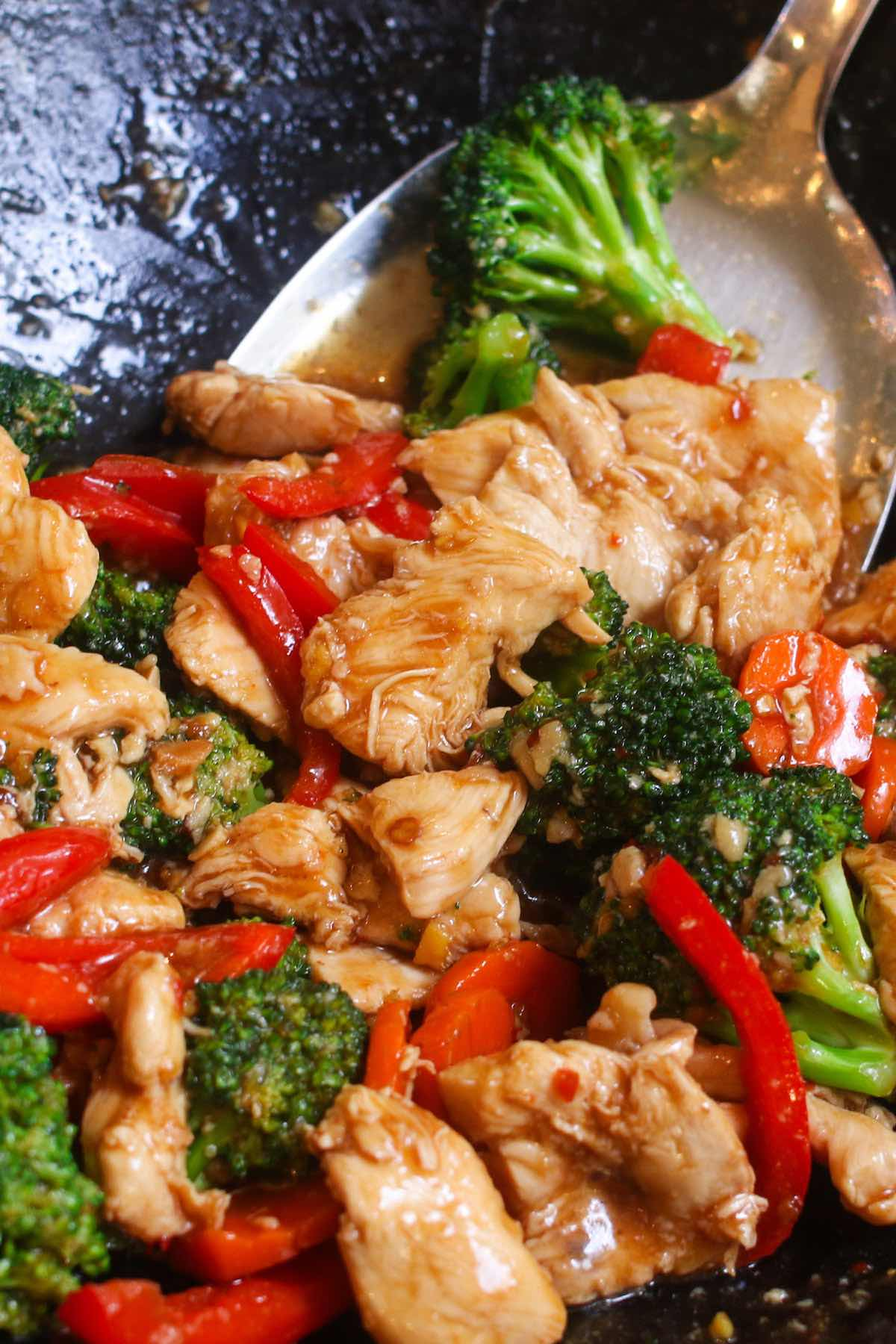 Closeup of Hunan chicken in a wok before serving showing juicy slices of chicken with broccoli, carrots and red bell pepper in a spicy hunan sauce