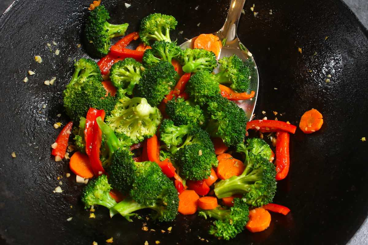 Stir frying broccoli, carrots, red bell pepper and minced garlic in the wok.