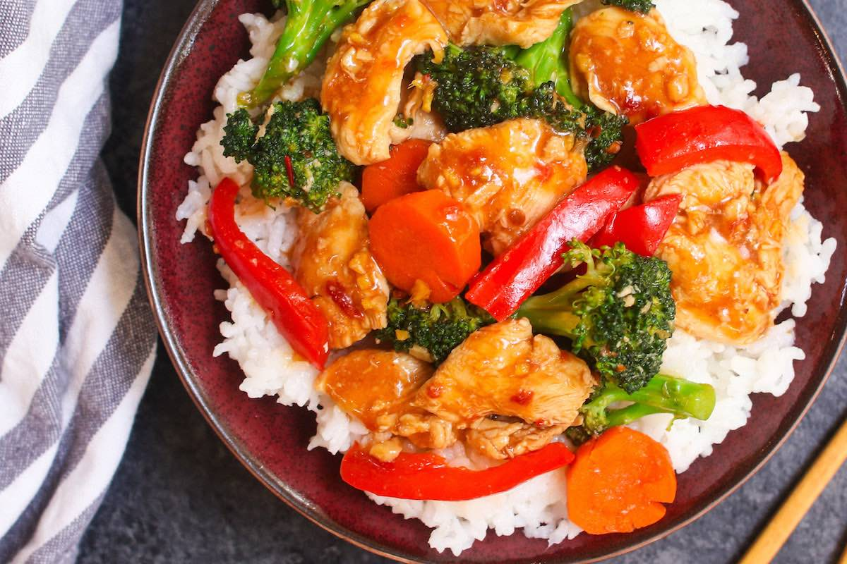 Closeup of a Hunan Chicken recipe served in a rice bowl