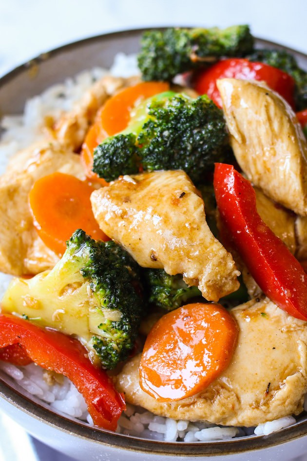 Closeup of hunan style chicken made with broccoli, carrots and red peppers and served in a rice bowl