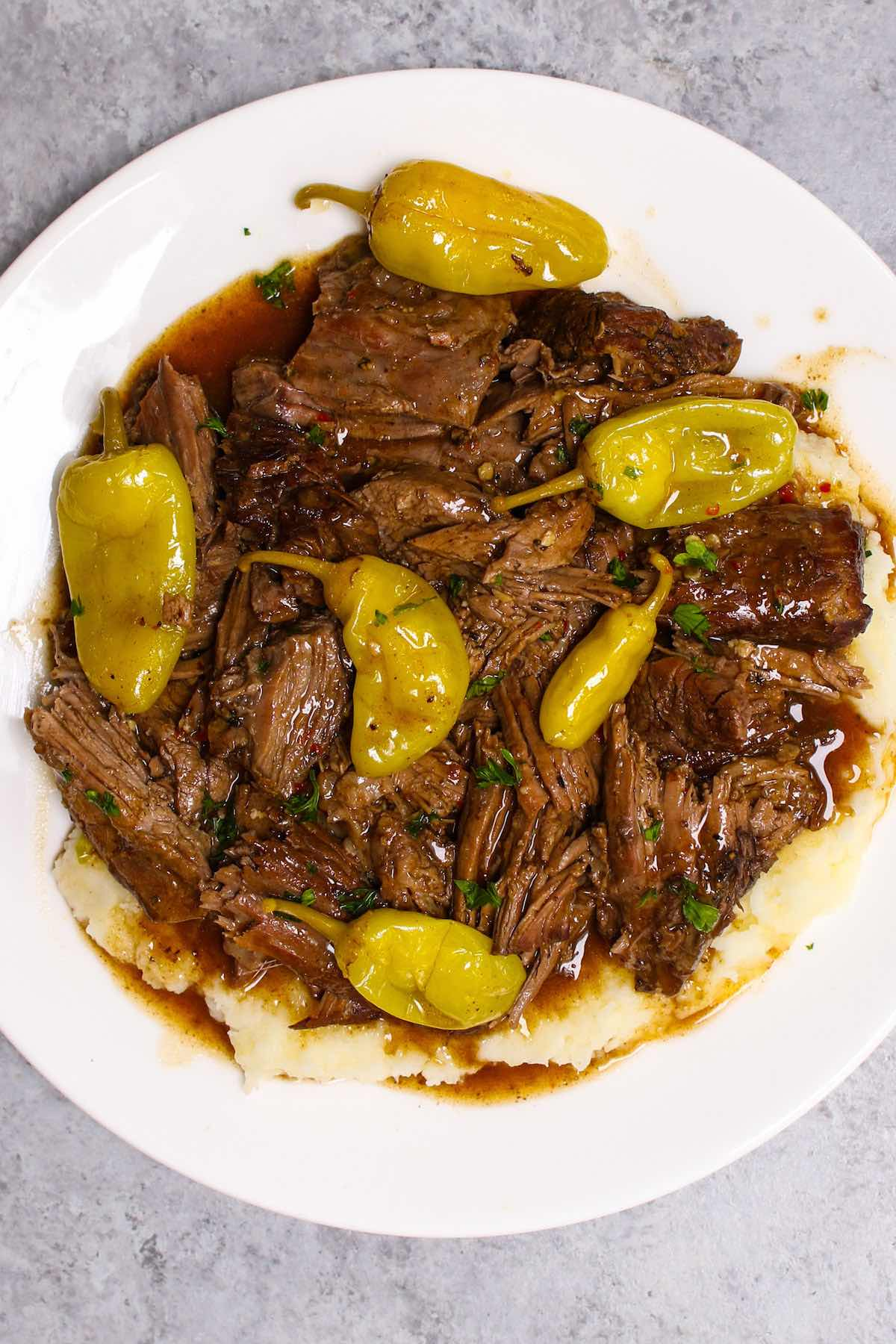 Instant pot Mississippi pot roast served over mashed potatoes, drizzled with delicious gravy on a white plate.