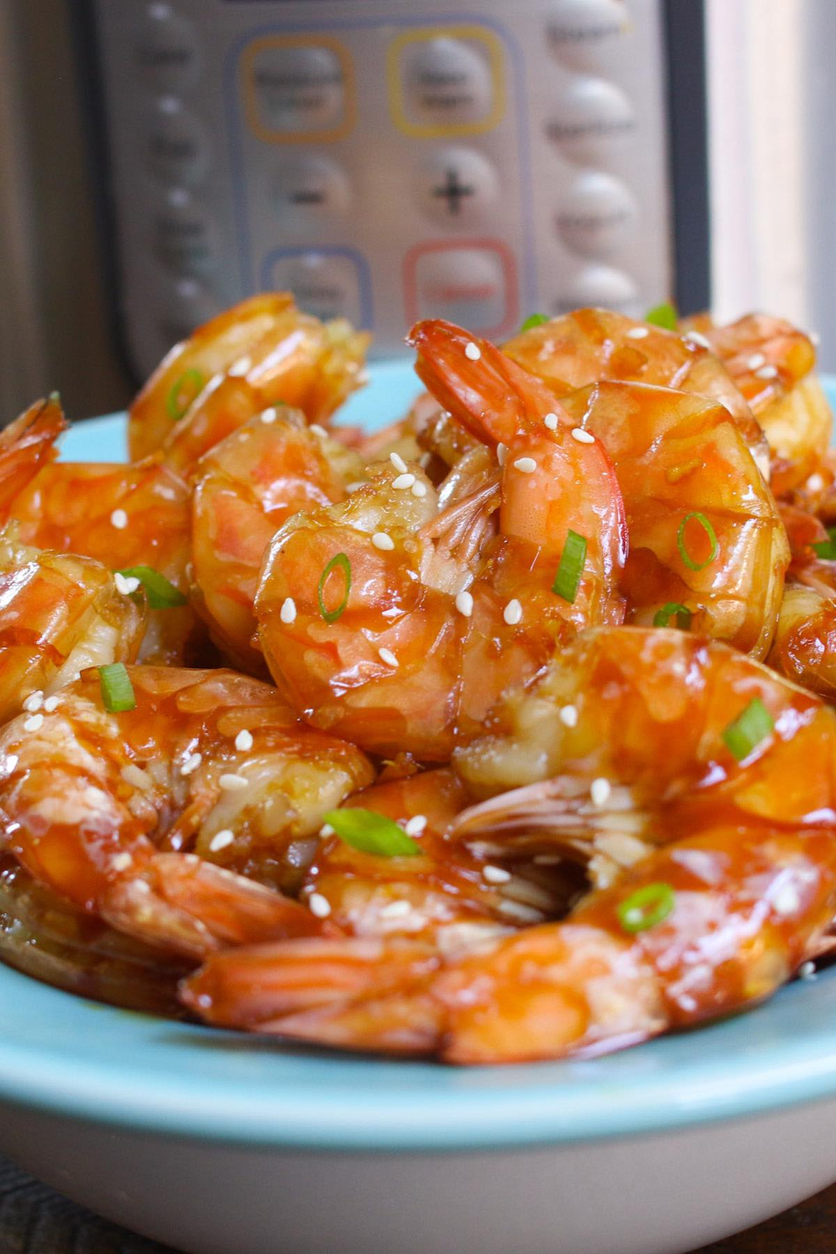 Instant Pot Shrimp with honey garlic sauce garnished with minced green onion and sesame seeds on a serving plate