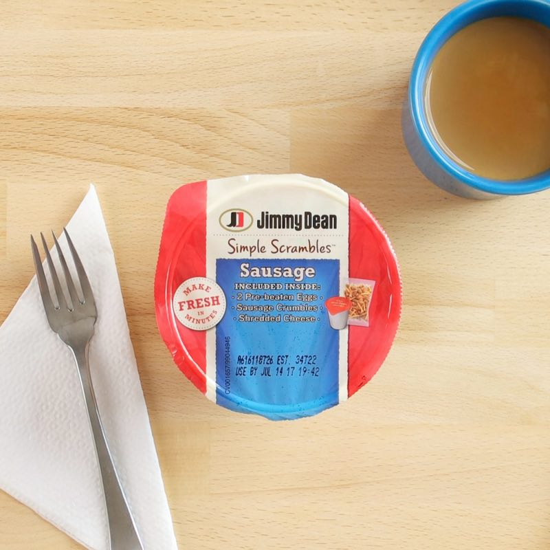 This is a close-up of the top of a Jimmy Dean Simple Scrambles package with a fork and napkin on a desk on a desk at the office ready to be prepared