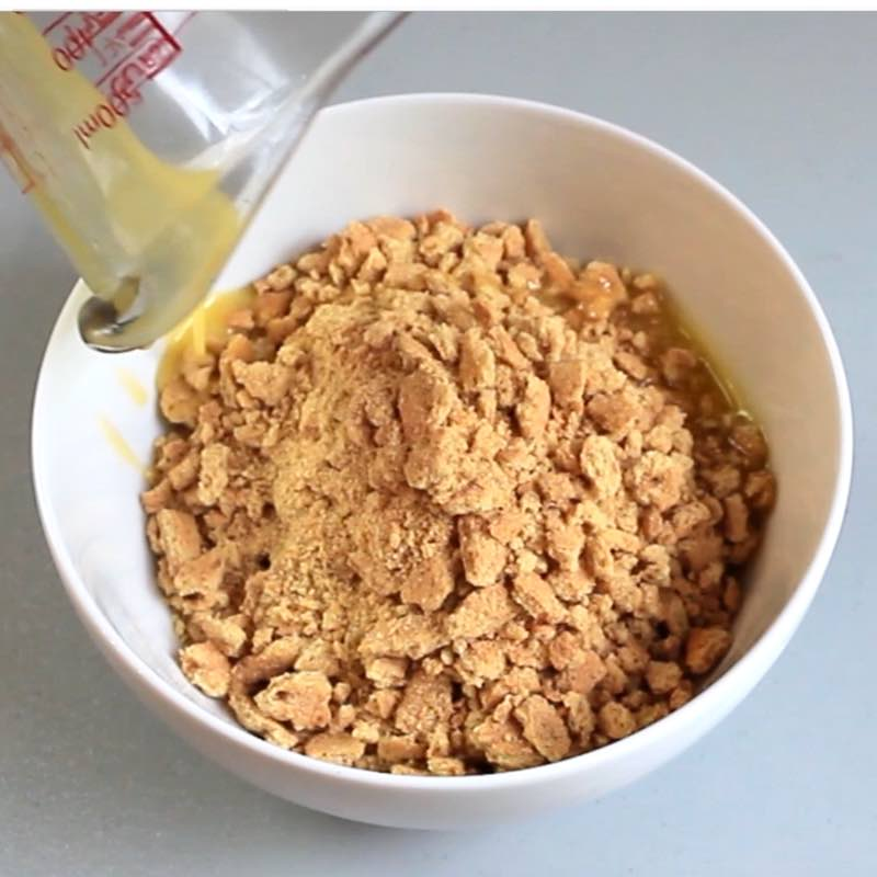 Making a graham cracker crust by combining crushed graham crackers with melted butter in a bowl