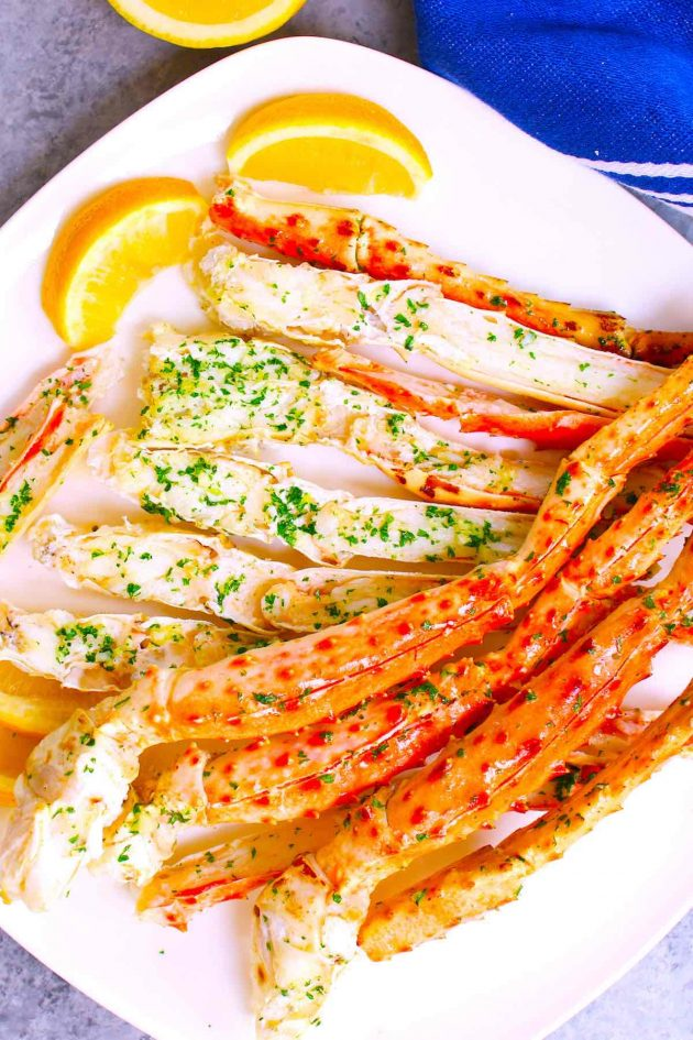 King crab legs served on a white plate with lemon wedges.
