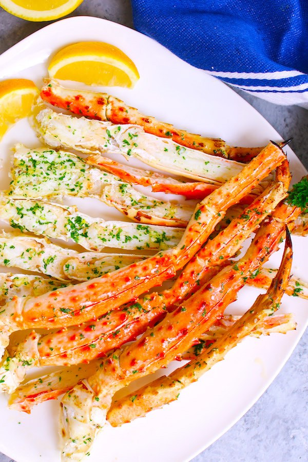 This is an overhead view of baked king crab legs with garlic butter arranged on a serving platter with lemon wedges ready to be eaten