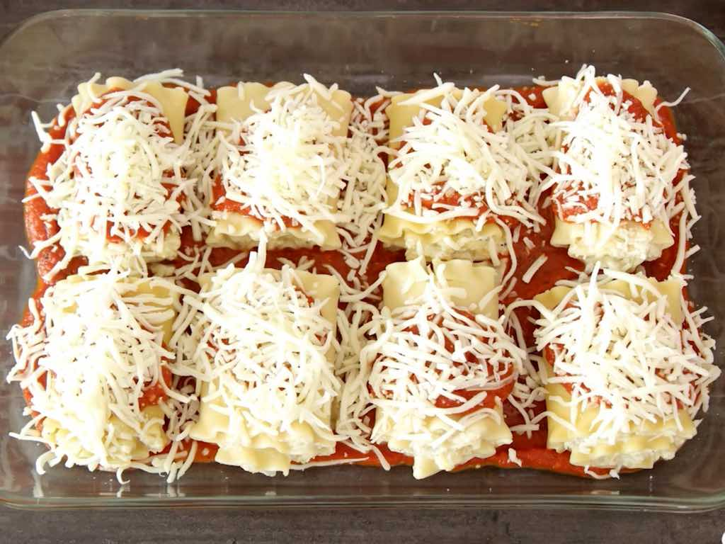 Zucchini Lasagna Roll Ups - this photo shows lasagna roll ups in a baking pan covered in grated cheese ready to be baked
