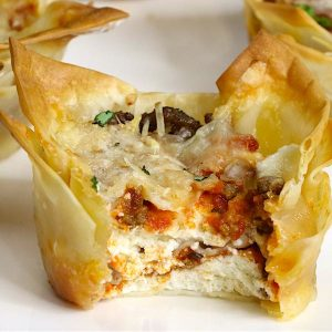 Bite shot of a mini lasagna cup showing the layers of meat and cheese