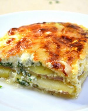 Cheesy Ham and Potato Casserole – you can't resist this simple, classic layered ham and cheese bake that's easy to make for brunch, lunch or dinner! All you need is a few ingredients: potatoes, ham, swiss cheese, parsley, eggs and half and half milk. Quick and easy dinner idea. Video recipe. | tipbuzz.com