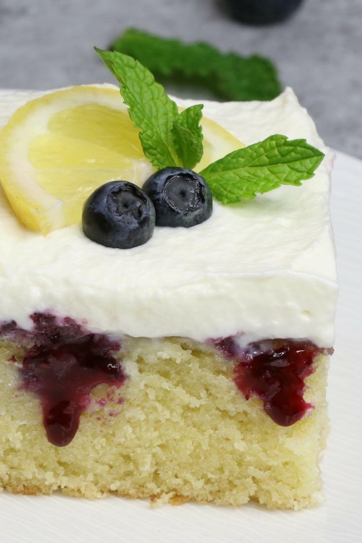 A serving of lemon blueberry poke cake garnished with fresh lemon and mint
