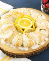 Quick And Easy Lemon Cheesecake Crescent Ring (video recipe) - bursting with irresistible lemon flavour! Tender and flaky crescent ring filled with creamy lemon cheesecake and topped with lemon zest! All you need is a 7 simple ingredients: cream cheese, lemon juice, lemon zest, sugar, crescent roll dough and milk. Perfect for Easter or any holiday breakfast or brunch! Vegetarian. | tipbuzz.com