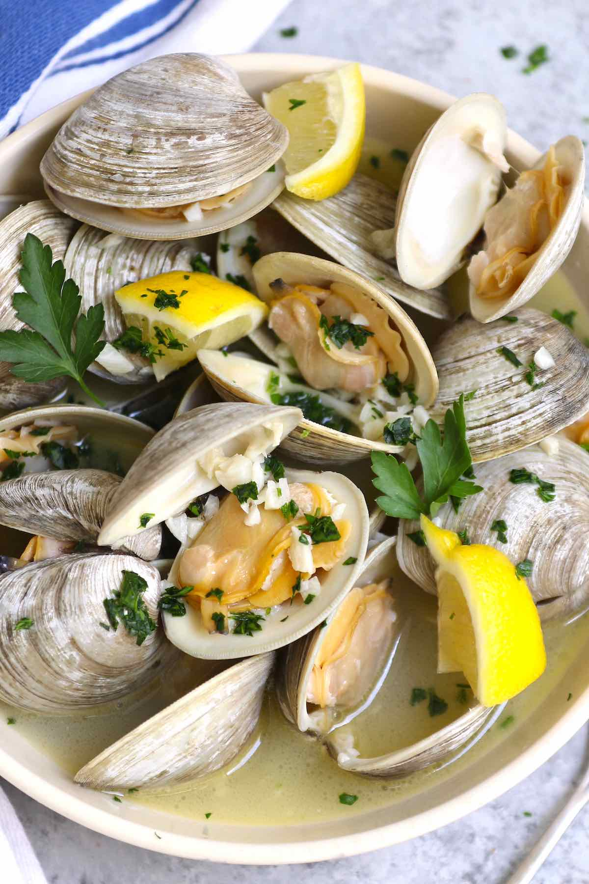 A serving of little neck clams with lemon wedges and fresh herbs