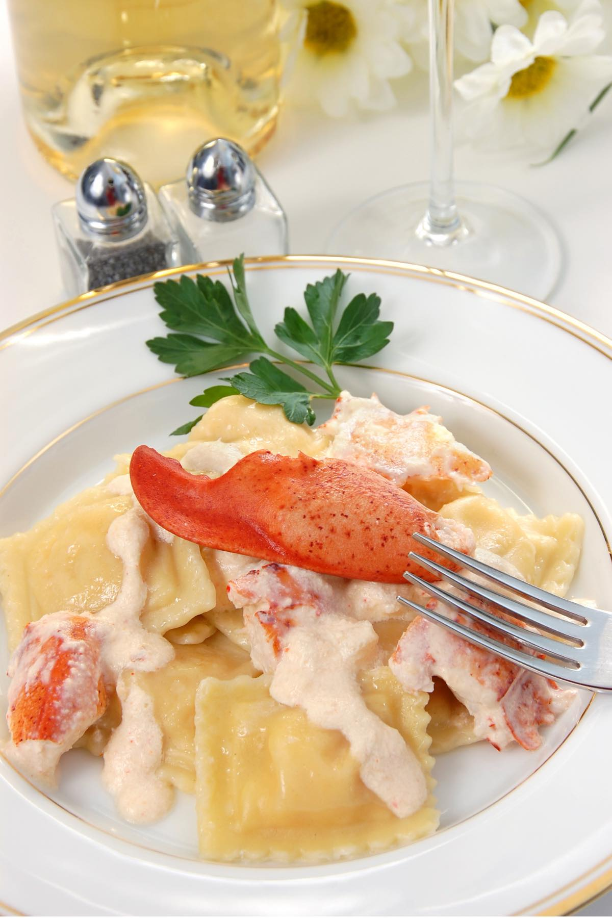 A serving of lobster ravioli with a rose-colored cream sauce and garnished with fresh lobster meat