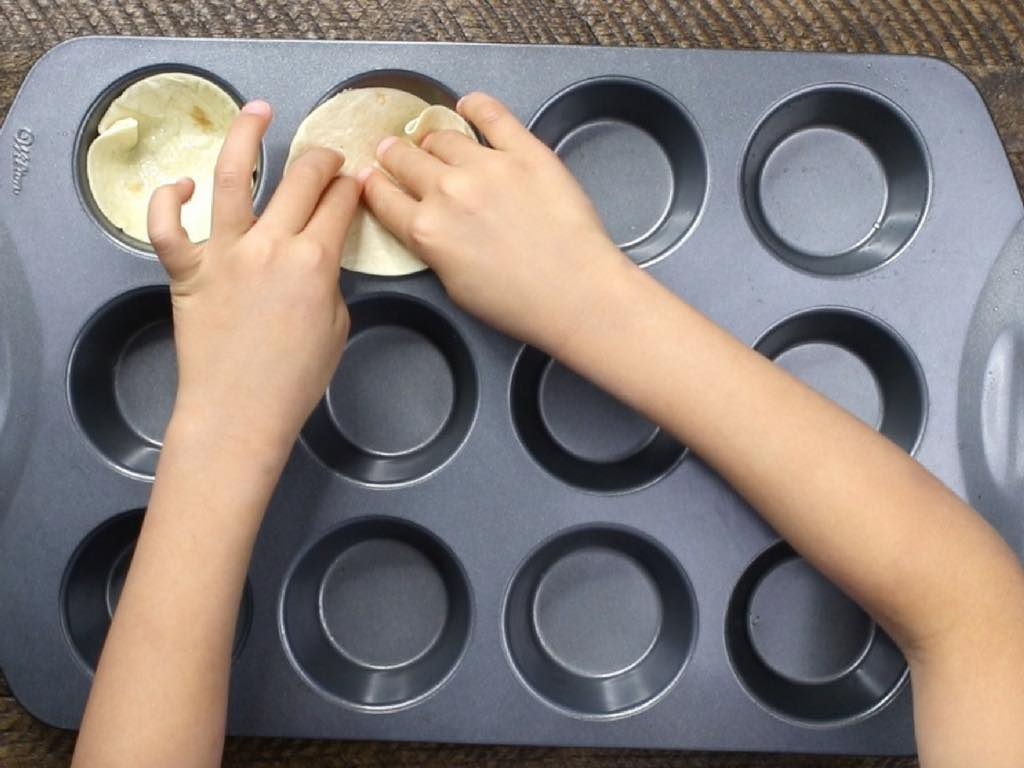This is a process photo showing pressing tortilla cutouts into a muffin pan to bake